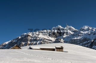 Kleine Berghütten auf einer Alp vor dem Säntismassiv im Winter, Schweiz