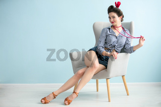 Beautiful retro girl with slender legs sits in a chair.Vintage woman.