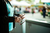 Hands of an elderly woman holding pen