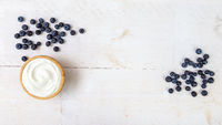 Heap of juicy blueberries and wooden bowl of smooth white yoghurt on white table