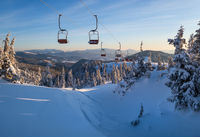 Alpine resortr ski lift with seats going over the sunrise mountain skiing freeride slopes and fir tree groves