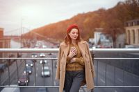 Portrait of stylish young woman wearing autumn coat and red beret outdoors. Tender young woman warming up with cup of coffee on the street female fashion standing on a pedestrian bridge. Toned image