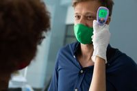 Mixed race woman wearing face mask checking temperature of male colleague