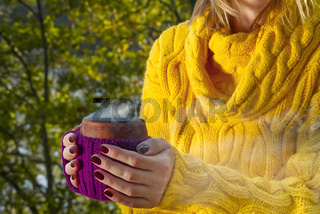 Close-up view of ceramic cup of hot coffee ortea in female hand. hot beverege drink in autumn park. warming warm drink in the autumn forest
