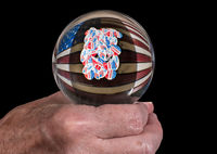 Senior mans hand holding a glass fortune telling ball to predict the results of the US election