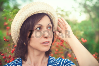 Image of beautiful middle-aged woman wearing straw hat looking aside while walking in summer park