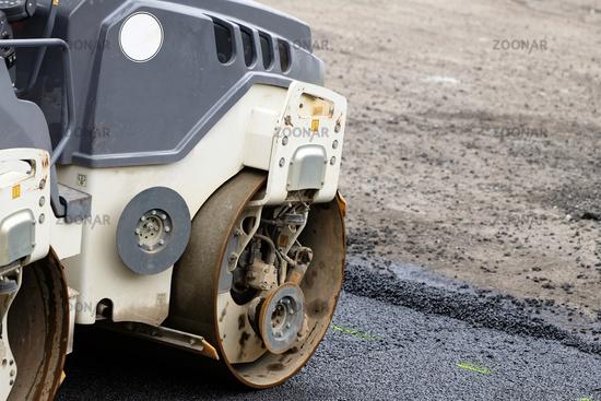 Tandem roller compacts asphalt