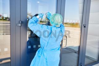 Reinigungskraft bei Desinfektion von Tür einer Klinik wegen Coronavirus