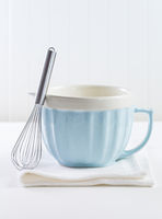Blue mixing bowl with wisp for baking on white background. Kitchen utensil for cooking and baking.