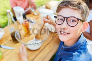 Fröhlicher Junge bereitet Salatsauce zu im Kochkurs