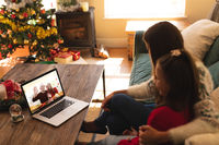 Woman and daughter sitting on the couch having a videocall with couple in santa hats waving on lapto
