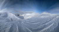 Snow covered fir trees on snowy mountain plateau, tops with snow cornices in far. Magnificent sunny day on picturesque beautiful alps ridge. High resolution panorama.