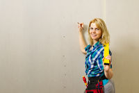 Blond woman wearing a DIY tool belt full of a variety of tools on a unpainted plasterboard wall background. Construction woman concept.