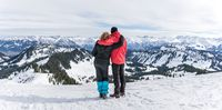Senior couple is hiking in alpine snow winter mountains enjoying panorama view. Allgau, Bavaria, Germany.