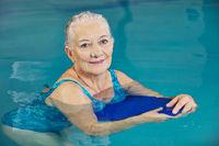 Seniorin macht Aquafitness im Schwimmbad