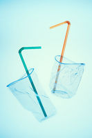 Squashed plastic cups and drink straws over blue background