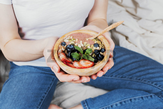 Closeup of woman in jeans and white shirt in her bed holding vegan smoothie bowl