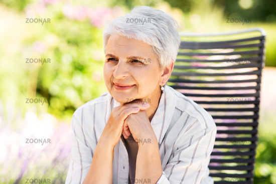 happy senior woman resting at summer garden