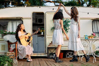 Young happy women have fun together playing guitar and dancing outdoors near their camper van