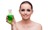 Woman holding a bottle of green perfume
