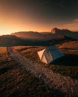Tent in mountains at beautiful sunrise in dolomites