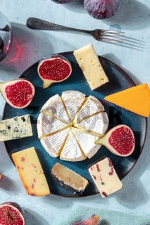 Cheese selection, overhead vertical shot on a plate with fresh figs