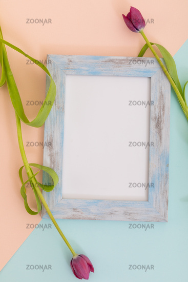 Rustic wooden frame with white background and pink tulips on blue and orange