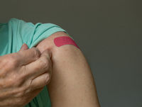 Senior man holding up shirt after covid-19 vaccine injection