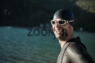 triathlon athlete starting swimming training on lake
