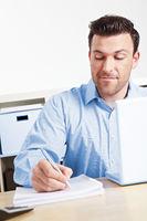 Mann im am Schreibtisch macht Notizen