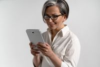 Portrait of a grey haired senior woman in white shirt and eye glasses using digital tablet. Technology by the elderly browsing internet shopping online using pad isolated on white background