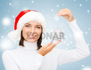 woman in santa helper hat with christmas ball