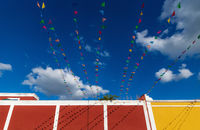 Vibrant flag chains over bright blue sky along colorful colonial building, Valladolid, Mexico