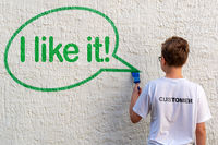 A young boy in front of a white house wall drawing a green speech bubble with text I LIKE IT