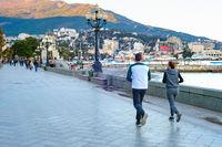 Couple jogging, cityscape, promenade Yalta