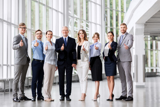 business people showing thumbs up at office