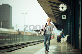 Blonde caucasian woman waiting at the railway station carrying bag