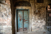 Old blue door of a abandoned house. Old door design. The rear entrance to the castle. Vintage door of old building. Traditional doors in the old city