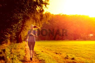 Junge Frau joggt an einem Waldweg