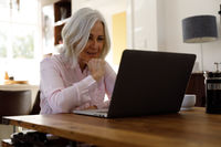 Senior caucasian woman having a video chat on laptop while working from home