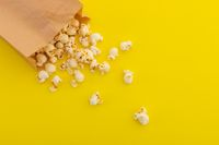 High angle view of popcorn spilling out of brown paper bag on yellow background