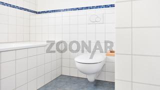 Saubere WC Toilette im Bad neben Badewanne mit weißen Fliesen