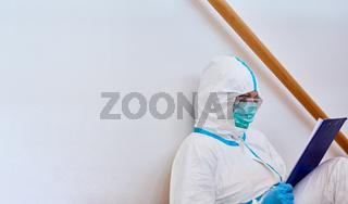 Pflegepersonal in Klinik in Schutzkleidung studiert Liste in Pause auf Boden