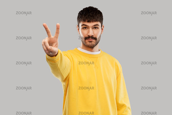 young man showing peace over grey background