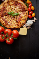 Delicious italian pizza served on black wooden table