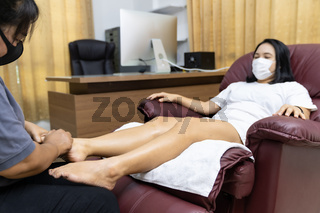 New Normal Asian woman with face mask do massage at home