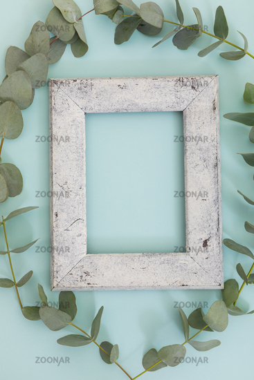 Rustic wooden frame surrounded by green leaves on green background