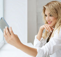 Sexy girl in white shirt making selfie in studio