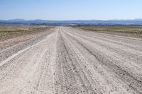 Landscape with straight road to the horizon and oncoming traffic, Namibia, Africa.