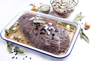 Marinated traditional German Sauerbraten from beef with onion and spice as closeup in a white skillet - isolated